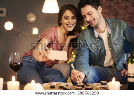 Couple enjoying sushi together at home interior