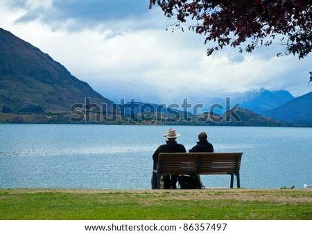 Couple enjoying the view of Lake Wanaka in  New Zealand on an overcast day