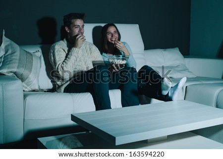 Couple Enjoying Watching A Movie At Home Laughing On The Couch Stock Photo 163594220  Shutterstock