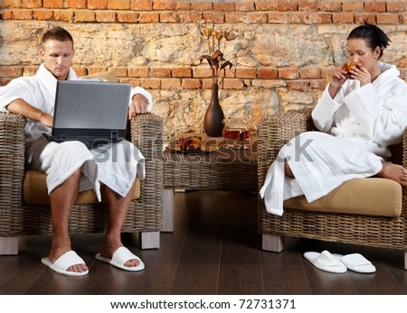 Couple enjoying wellness room in bathrobe, sitting together in armchair, using laptop computer, having tea.?