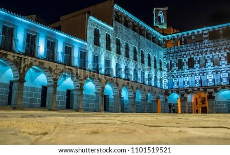 Couple entering at Hight square of Badajoz,  illuminated by led lights at night. Soft noise at 100%