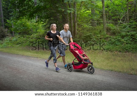 Couple exercising and jogging together pushing their baby in a stroller
