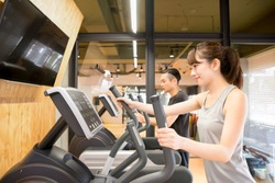 Couple exercising on cross trainers together