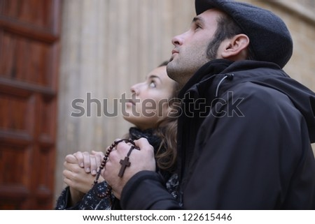 Couple facing the church door, praying with rosary in hand