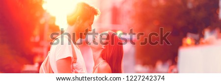 Couple falling in love dating laughing having fun on summer outdoor date in sunset. Panorama banner. Interracial young couple attracted looking into each other's eyes. Asian girl, Caucasian man, 20s.