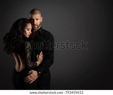 Couple Fashion Portrait, Young Man Embrace Beautiful Woman in Elegant Black Dress #793459612