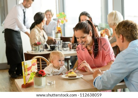 Couple feeding their child cake at cafe restaurant woman man
