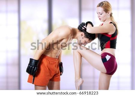 Couple fighters - woman instructor and men training mixed martial art. kickboxing;  muay thai; taekwondo; Jiu-jitsu; kungfu or mma. Kick knee in hand