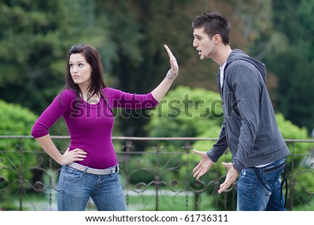 Couple fighting. A young man is trying to apologize, while his girlfriend doesn't want to hear it
