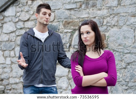 Couple fighting. A young man is trying to have a conversation, while he's been ignored by his girlfriend