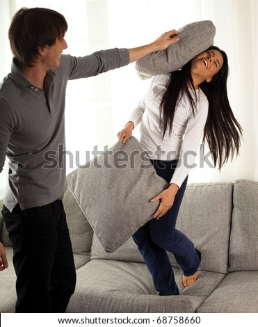 stock photo : couple fighting with pillows on the sofa