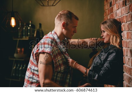 Couple flirting at bar, looking at each other with desire