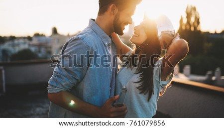 Photo of  Couple flirting while having a drink on rooftop terrasse