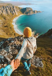 Couple follow me holding hands hiking in  mountains above ocean beach friends traveling together in Norway adventure lifestyle outdoor summer vacations aerial view