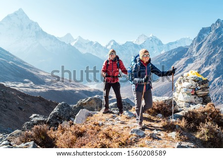 Couple following Everest Base Camp trekking route near Dughla 4620m. Backpackers carrying Backpacks and using trekking poles and enjoying valley view with Ama Dablam 6812m peak