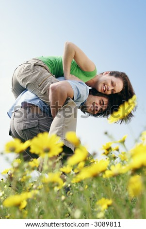 couple fooling around in a field of flowers