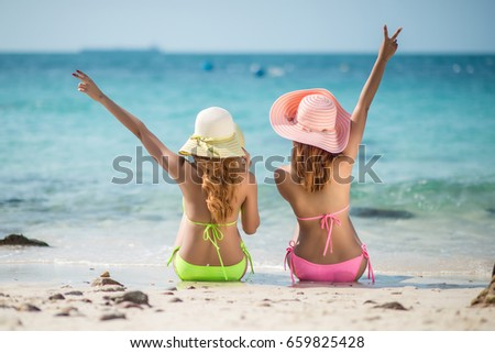 Couple friends, Asian women  happy on the beach during at summer vacations; summer holidays, travel, people and vacation concept. #659825428