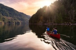 Couple friends canoeing on a wooden canoe during a colorful sunny sunset. Cloudy Sky Artistic Render. Taken in Harrison River, East of Vancouver, British Columbia, Canada.
