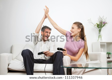 Couple giving a high-five to each other while having great time playing video game together