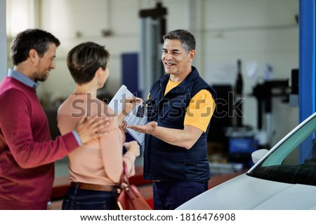Couple giving car keys to their auto mechanic in auto repair shop. Focus is on mechanic.  Foto stock ©