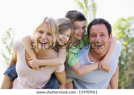 Couple giving two young children piggyback rides smiling - stock photo