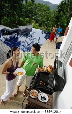 Couple grilling food over barbeque #585912014