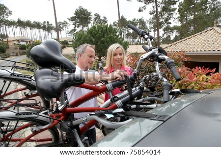 Couple hanging bicycles on bike carrier