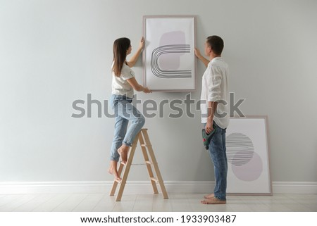 Couple hanging picture on wall together in room. Interior design Foto stock ©