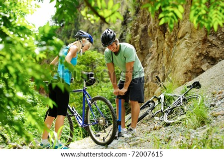 Couple have a flat tyre with mountain bike outdoor in the wilderness