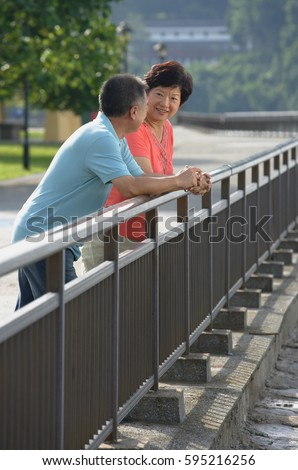 Couple having a conversation while leaning in fence