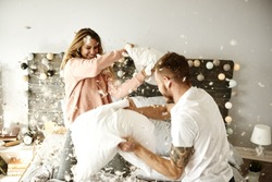 Couple having a fun while pillow fight
