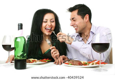 Couple having a romantic dinner with a grilled steak and a bottle of red wine.
