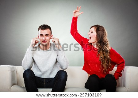 couple having argument - conflict, bad relationships. Angry fury woman screaming man closes his ears.