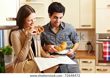Couple having breakfast in the kitchen with pretzel and croissant