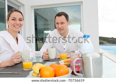 Couple having breakfast in their home terrace