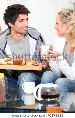 Couple having breakfast together on sofa