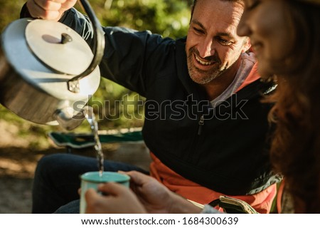 Couple having coffee while camping in nature. Man pouring coffee in woman's cup. stock photo