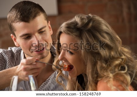 Couple having dinner in a restaurant - man feeding his woman and both having fun