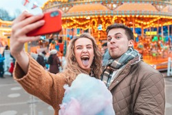 Couple having fun and taking a selfie at amusement park in London - Young man and woman making funny faces at camera and eating cotton candy at funfair - Happy lifestyle and love concepts