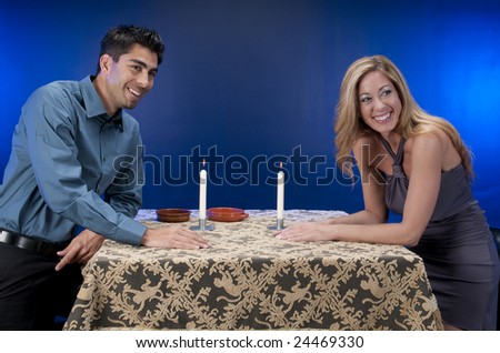 Couple having fun in a restaurant or night club atmosphere. Young adult male with mature woman.