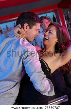 Couple Having Fun In Busy Bar
