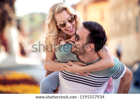 Couple having fun.Man giving piggyback ride to woman in the city. #1195557934