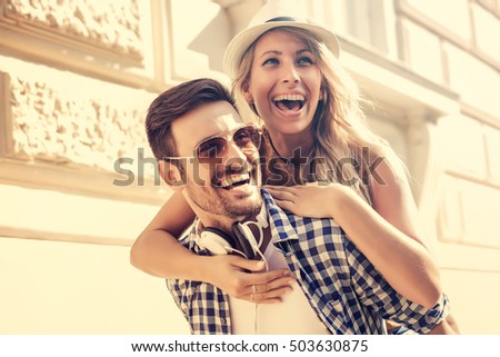 Couple having fun.Man giving piggyback ride to woman in the city. #503630875