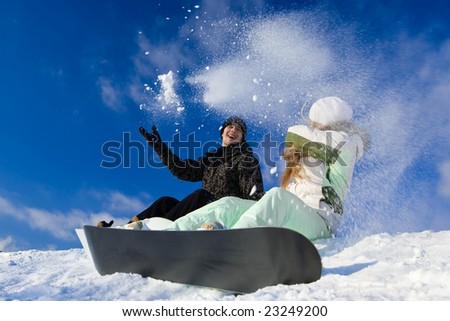Couple having fun on snowboards at winter day