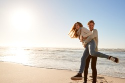Couple Having Fun On Winter Beach Together