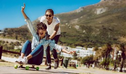 Couple having fun outdoors near the beach. Man pushing her girlfriend on a skateboard.