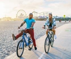 couple having fun riding bikes together at santa monica california