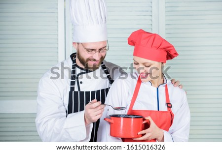 Couple having fun while whipping cream. Woman and bearded man chef cooking together. Cooking healthy meal. Delicious meal. Baking pie together. Cooking together is more fun. Let my try taste.