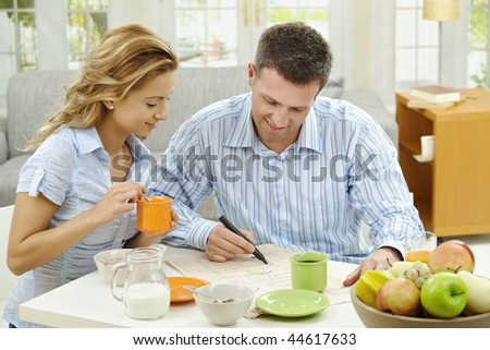 Couple having healthy breakfast at home, reading and  marking newspaper article.