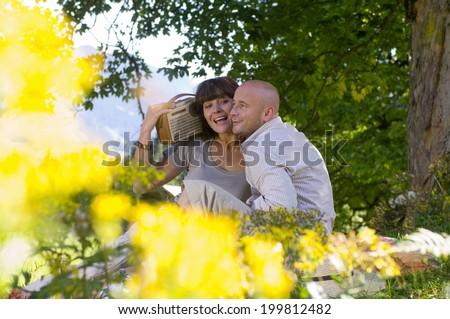 Couple having picnic under tree, listening to radio